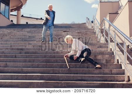 Terrible accident. Slender elderly woman lying on the stairs, having fallen down, while a man standing a couple of steps higher screaming in surprise