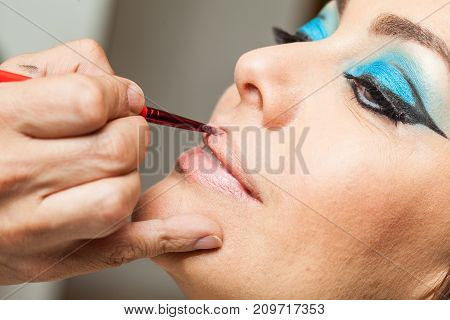 Makeup Artist Applying Lipstick To A White Woman
