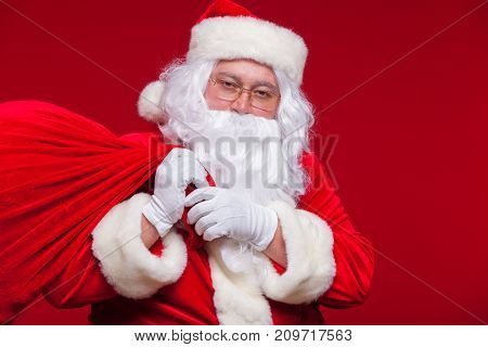 Portrait of Santa Claus with huge red sack keeping forefinger by his mouth and looking at camera.