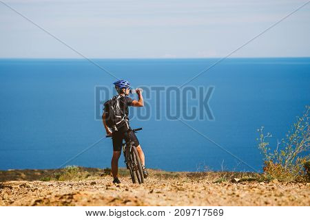 A Young Guy On A Mountain Bike Stopped To Drink Water From A Jar On A Stony Road Near The Mediterran