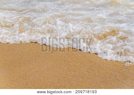 Foam wave on sea close with beach background