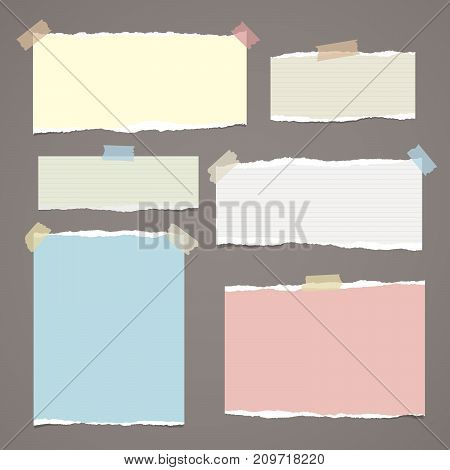 Colorful ripped paper strips, notebook sheets for note or message stuck with sticky tape on dark brown background