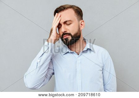 Bearded man in business clothes having headache and touching his forehead with closed eyes over gray background