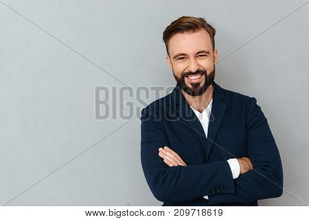 Happy bearded man in business clothes with crossed arms looking at the camera over gray background