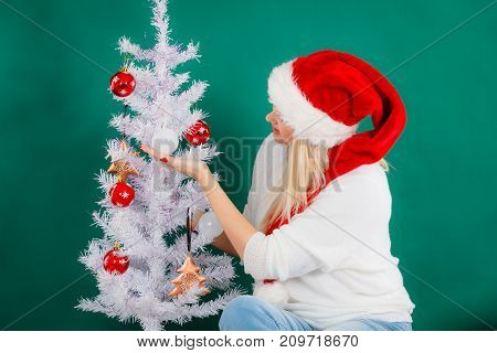 Woman In Santa Hat Decorating Christmas Tree