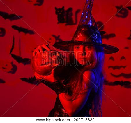 Little Girl In Witch Costume Playing On Red Background.