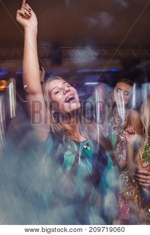 Joyful lady at Christmas discotheque. Active dancing girl with braces in night club in blurred motion, New Year company, modern youth life