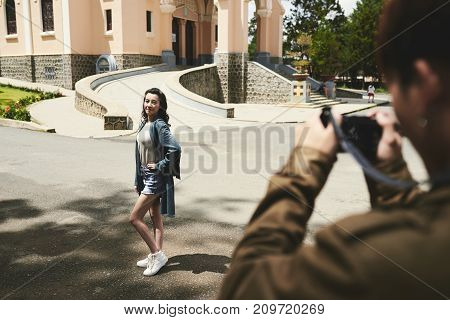 Pretty Vietnamese girl asking her boyfriend to take photo of her in the street