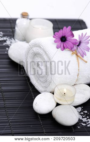 Spa setting with candle, rolled towel , Magnolia , salt, stoneson on mat