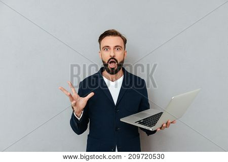 Shocked serious bearded man looking camera while holding laptop computer isolated over grey