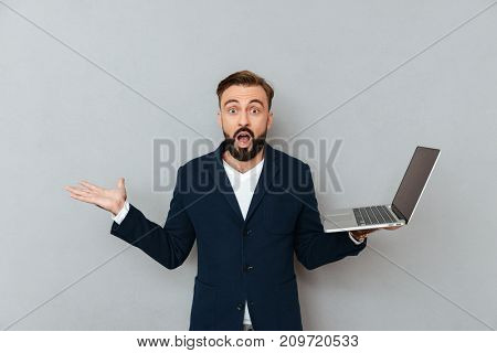Shocked bearded man in suit holding laptop computer and looking camera with opened mouth isolated over grey