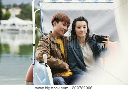 Smiling Asian young couple photographing during date in boat