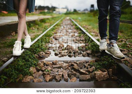 Legs of couple walking along train rails