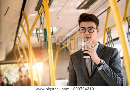 pensive young businessman in eyeglasses drinking coffee to go in bus