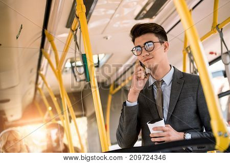 smiling young businessman in eyeglasses talking on smartphone and drinking coffee in bus