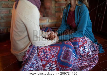 Couple in love sitting under warm blanket and holding hands