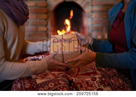 Hands of man giving Christmas surprise to his wife