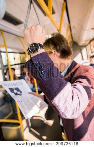handsome young businessman reading newspaper in bus