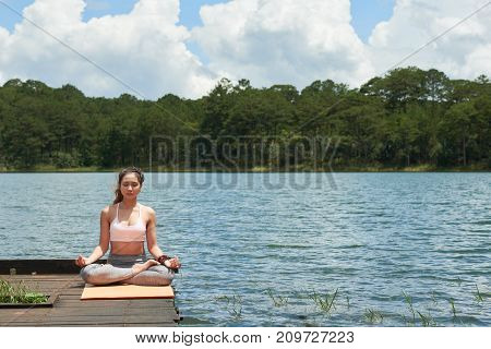 Pretty young woman sitting in lotus position on wooden pier by the lake