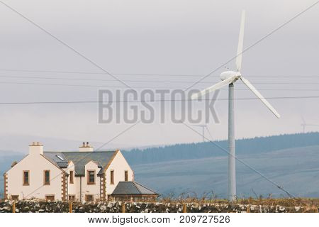 Modern house with wind turbines near mountains, telephoto shot