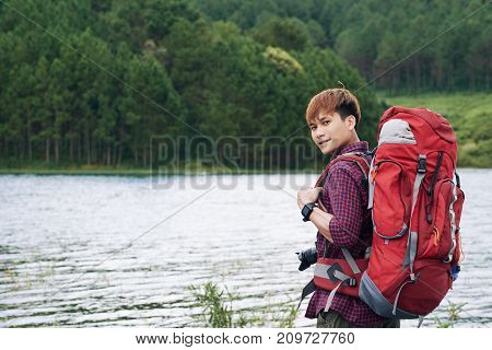 Portrait of handsome Asian young tourist with big red backpack