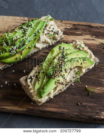 Hummus and avocado baguette sandwich with sesame and flax seeds on a wooden cutting board on a gray background. Healthy eating snack concept