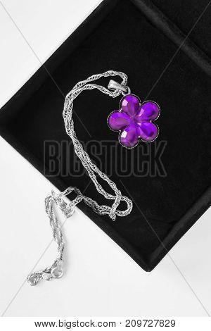 Purple amethyst flower pendant in black jewel box closeup