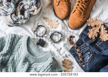 Flat lay women's clothing for autumn walks top view. Brown suede boots jeans a blue pullover scarf bracelets watches headphones perfume on a light background. Fashion concept