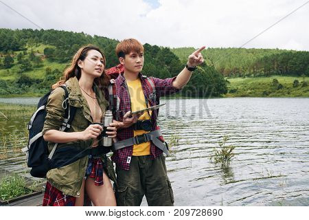 Asian young couple using map on digital tablet for orientation in mountains