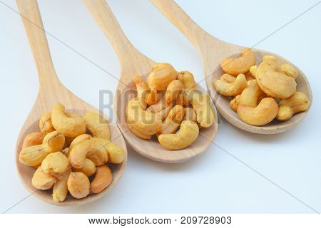 Roasted cashews. Organic roasted cashews In a wooden spoon