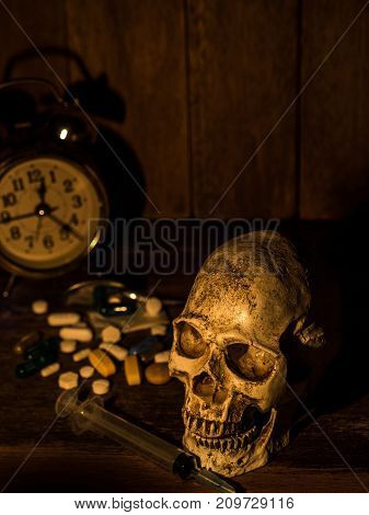 The skull is placed on a wooden table The back of skull is drug and clock. With candles light from the sides and a wooden background.