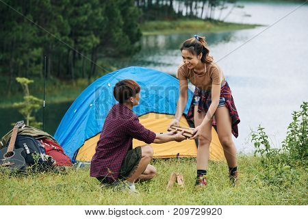 Smiling Vietnamese young woman bringing logs to her boyfriend who is making campfire