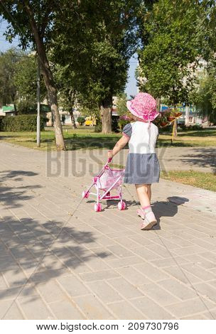 Baby girl playing with a baby stroller