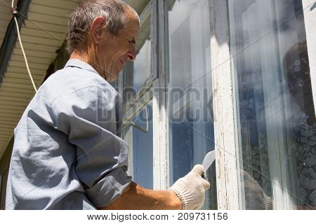 gray-haired man cleans the window from the paint