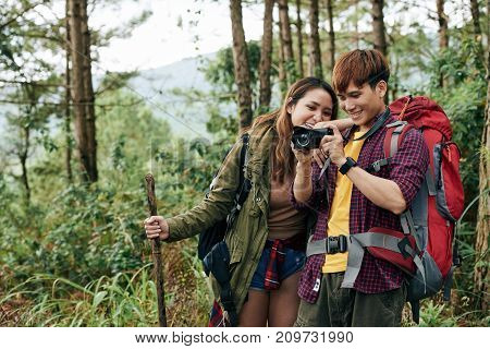 Cheerful Vietnamese young couple taking photos of nature