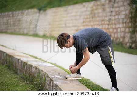 Jogger tying shoes before running in the street in the morning