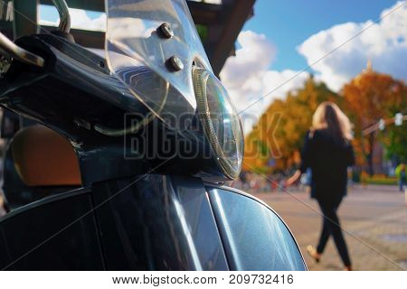 Scooter with a headlight parked against a background of an autumn city park with a passing girl with long hair