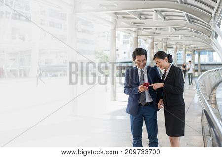 Asian businessman and businesswoman surf internet shopping online and chat with friend on mobile phone.with copy space for text