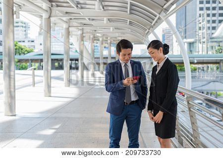 Asian businessman and businesswoman surf internet shopping online and chat with friend on mobile phone. with copy space for text