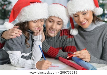 Portrait of young mother with kids preparing for Christmas