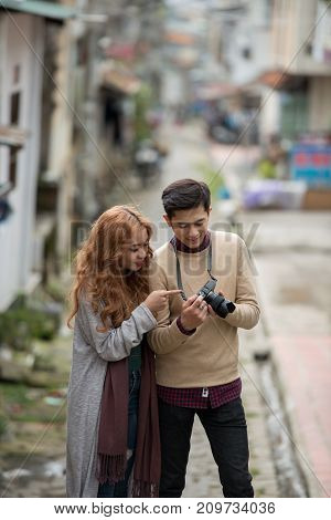 Young Vietnamese couple discussing photos they made during walk