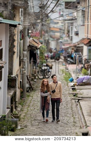 Asian young couple walking along little town street and looking around
