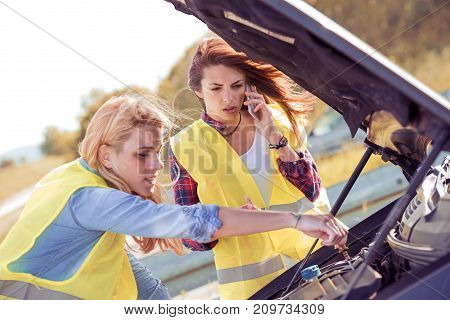 Portrait of a young girlfriends having some car trouble on a sunny day.