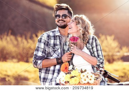 Young couple lovers having romantic moment with flower together in the park.