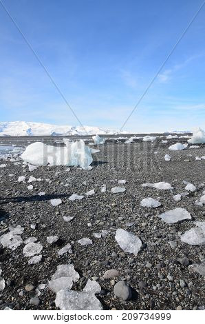 Blue skies with chunks of glaciers on a black sanded beach