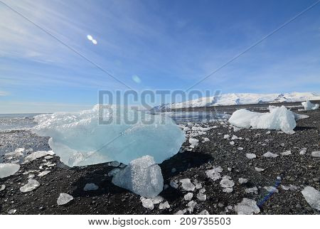 Glacial ice on the shore of a black sand beach