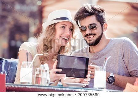 Beautiful young couple relaxing in the city and makes selfie at the restaurant.