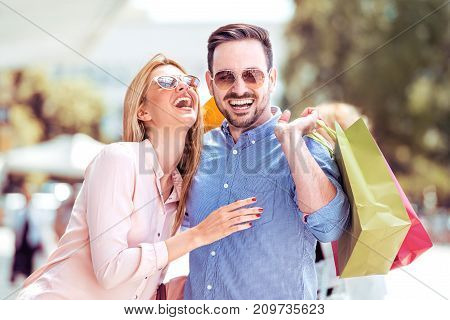 Beautiful young couple enjoying in shopping. Consumerism concept.