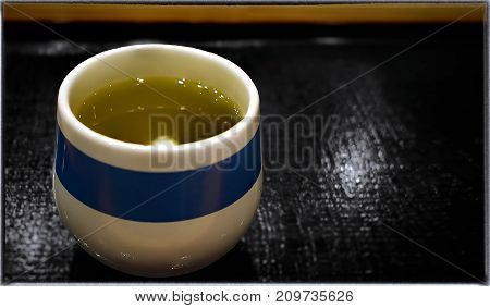Japanese Green Tea Served in a Japanese Cup on a Wooden Surface