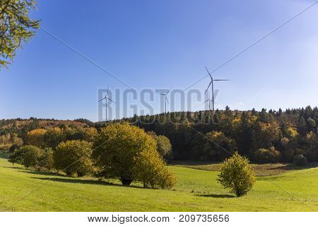 wind turbines in rural landscape to produce clean energy in close proximity to a natural conservation area forest hill meadow tree wildlife